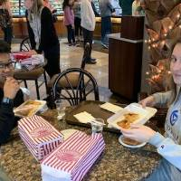 two students at a table in a bakery, eating dessert